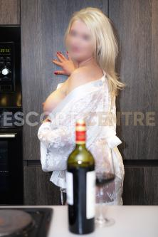 Monika in white frilly shirt is just about to open a bottle of wine