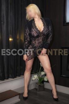 Escort Monika stands in black low cut blouse