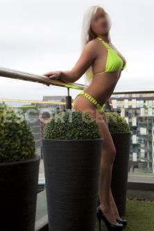 Abbey standing on a balcony in Bradford in a lime green bikini