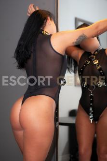 Black haired Robin in see through lingerie stands in front of mirror