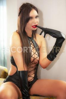 Elouie in a black lacy basque, pulling her latex glove from her hand with her teeth